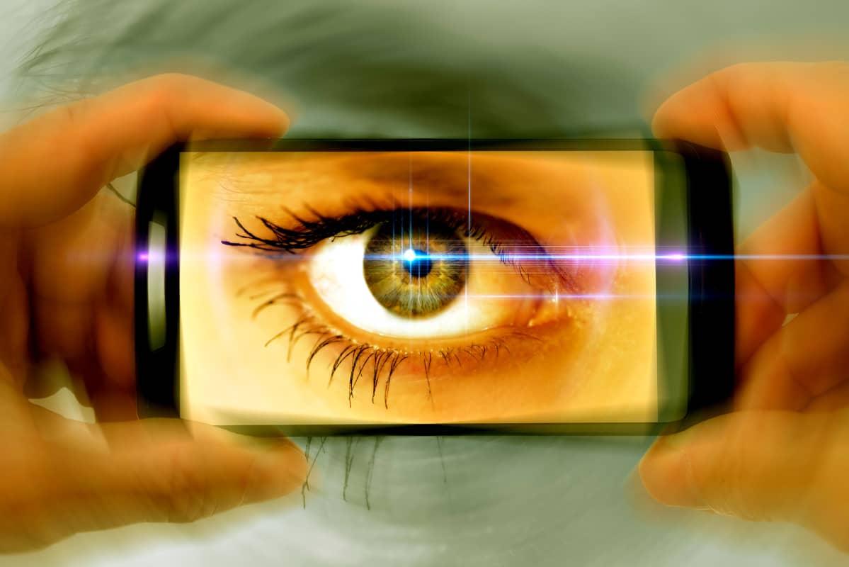 Älypuhelimen silmä katsoo katsojaa.
