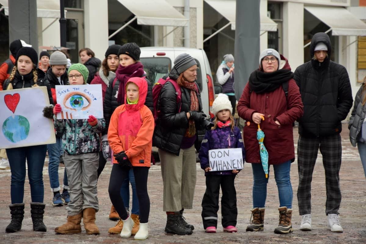 Eri-ikäiset ihmiset pitivät kylttejä kädessään Turun Vähätorilla.