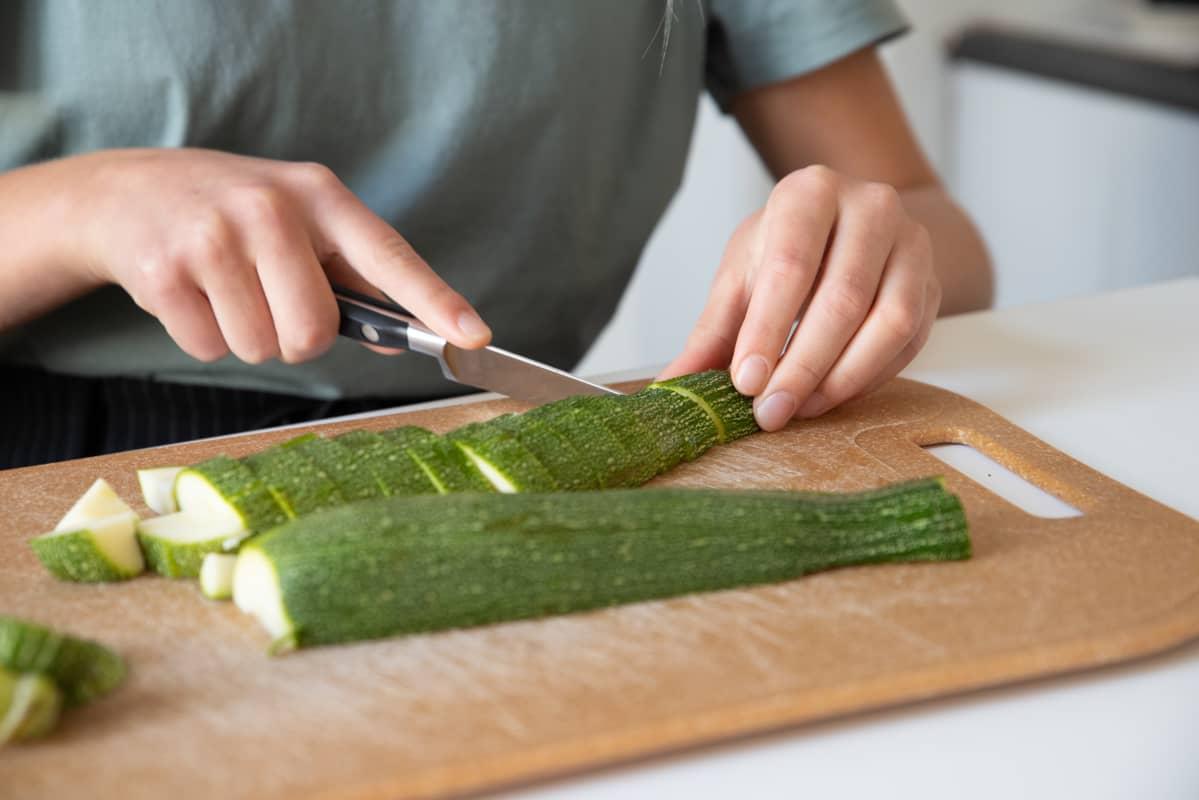 Nuori tyttö leikkaa kesäkurpitsaa.