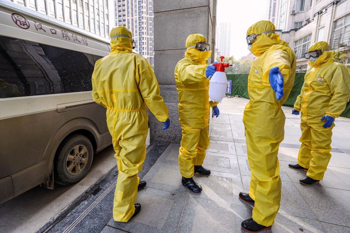 Suojavaatteisiin pukeutuneet hautaustoimiston työntekijät desinfioivat suojavaatteitaan sairaalan edustalla Wuhanissa.