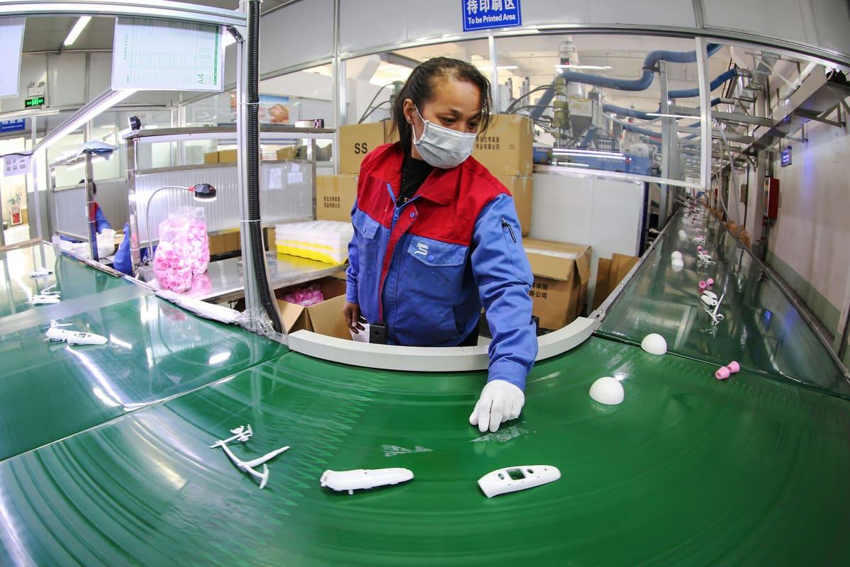 Työntekijä suojautui hengityssuojalla kiinalaisella tehtaalla Shandongin maakunnassa helmikuun alussa.