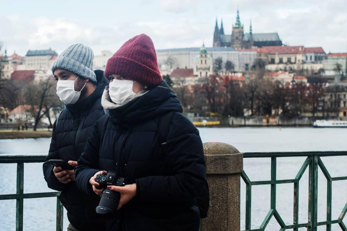Kuvassa on hengityssuojainta käyttäviä turisteja Prahassa.