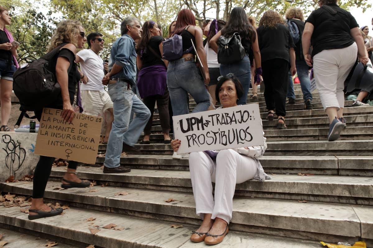 Mielenosoittaja istuu kyltin kanssa rappusilla