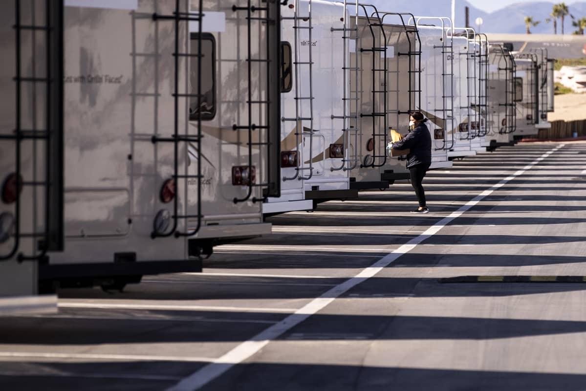Terveysviraston työntekijä valmistelee asuntovaunuja karanteeniin määrättyjä varten Kaliforniassa.
