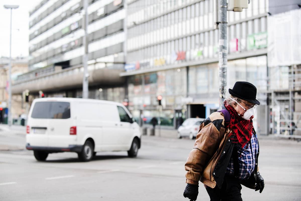 Hengityssuojaan pukeutunut mies kävelee kadulla Helsingissä.