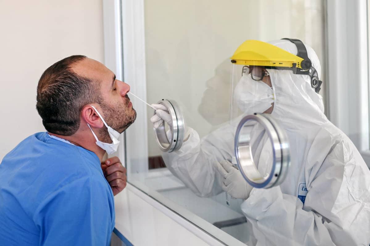Suojavarusteisiin pukeutunut terveydenhuollon työntekijä ottaa koronavirustestiä nenästä.
