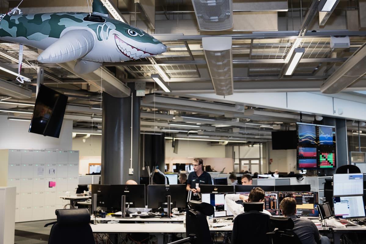 OP:n dealingsalissa istuu muutamia ihmisiä näyttöjen ääressä. Salin kattoon on ripustettu suurikokoinen ilmalla täytetty muovinen hai, joka irvistää ahneesti.