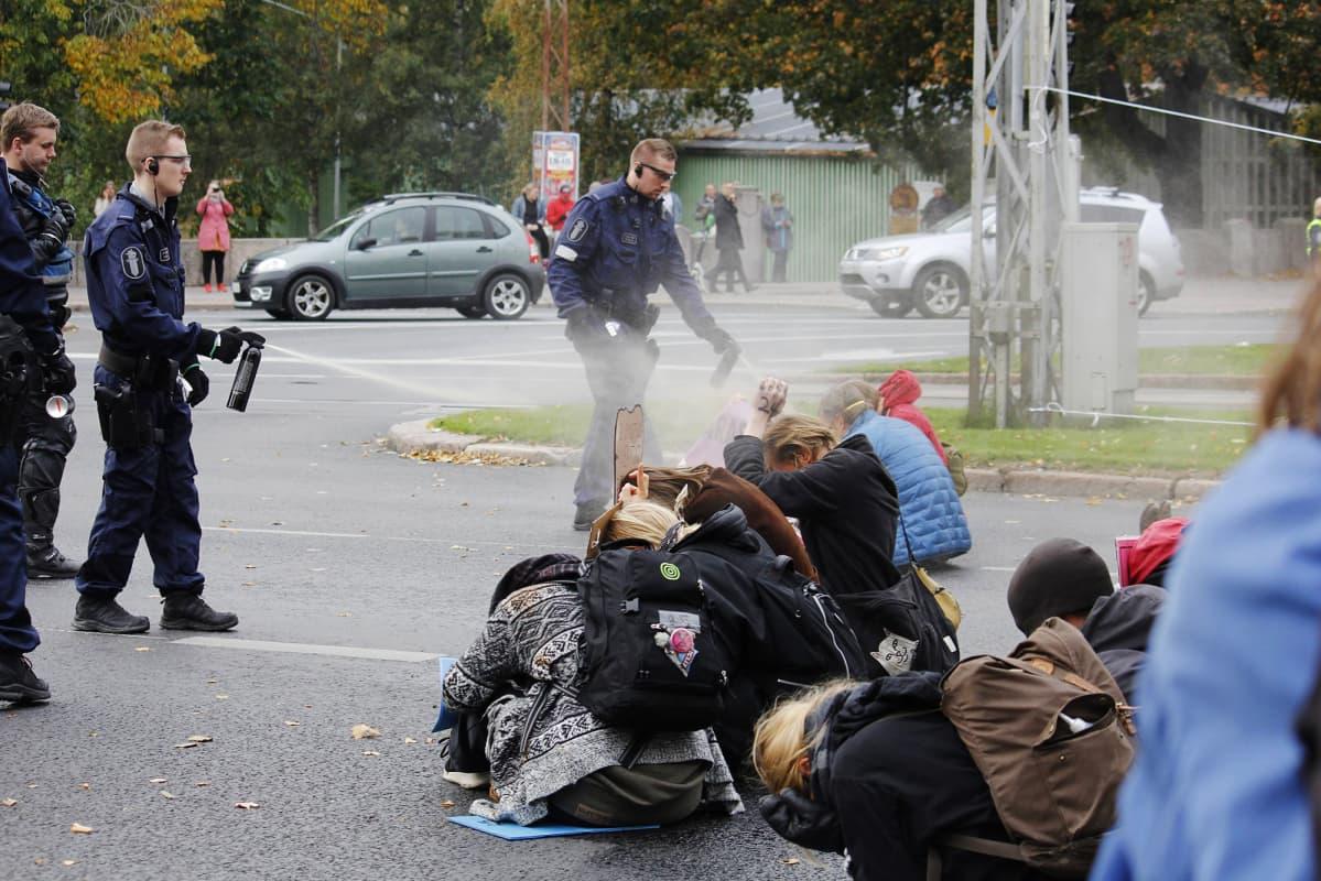 Kuvassa poliisi kaasuttaa mielenosoittajia Helsingissä.