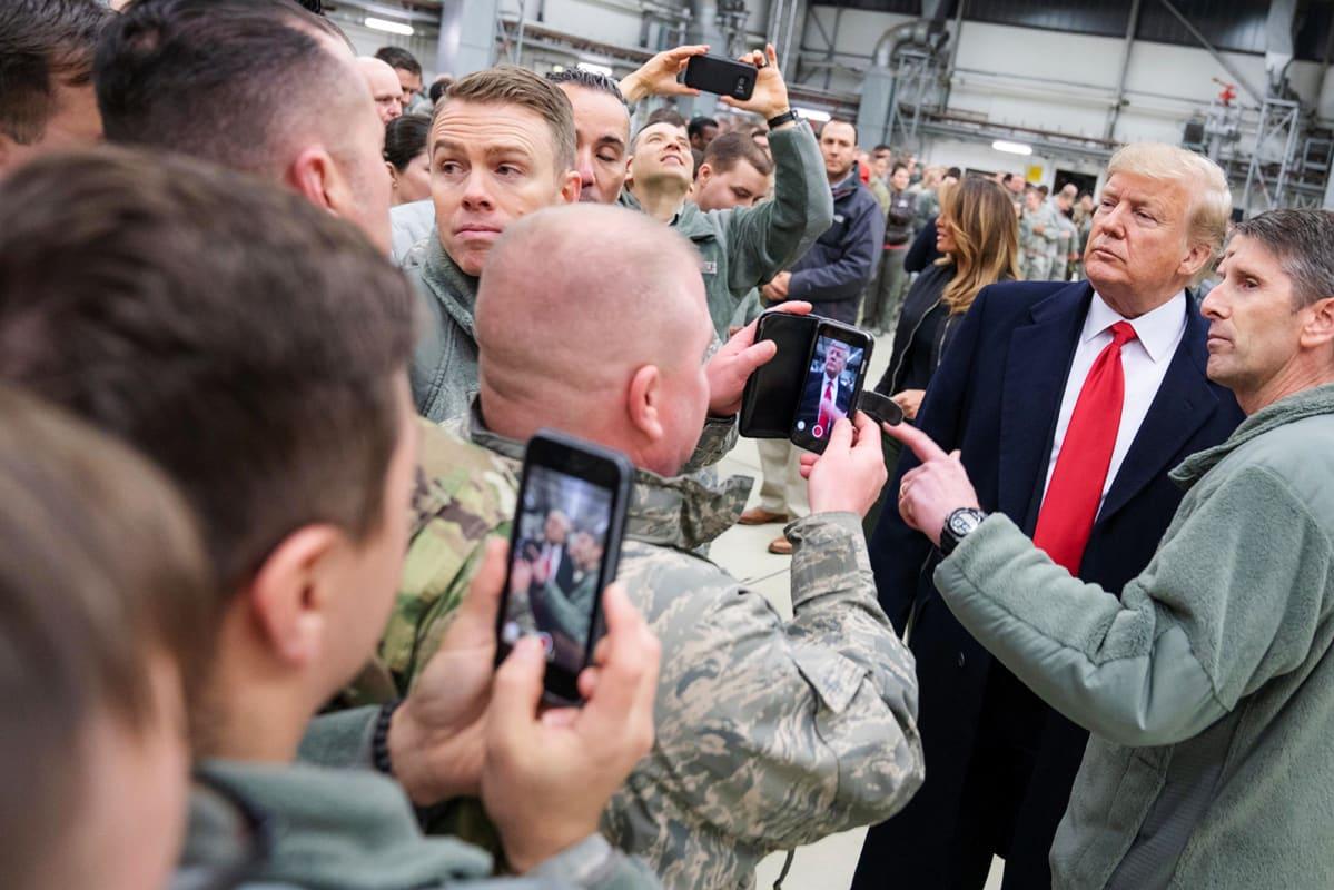 Kuvassa on Donald Trump ja amerikkalaisia sotilaita.