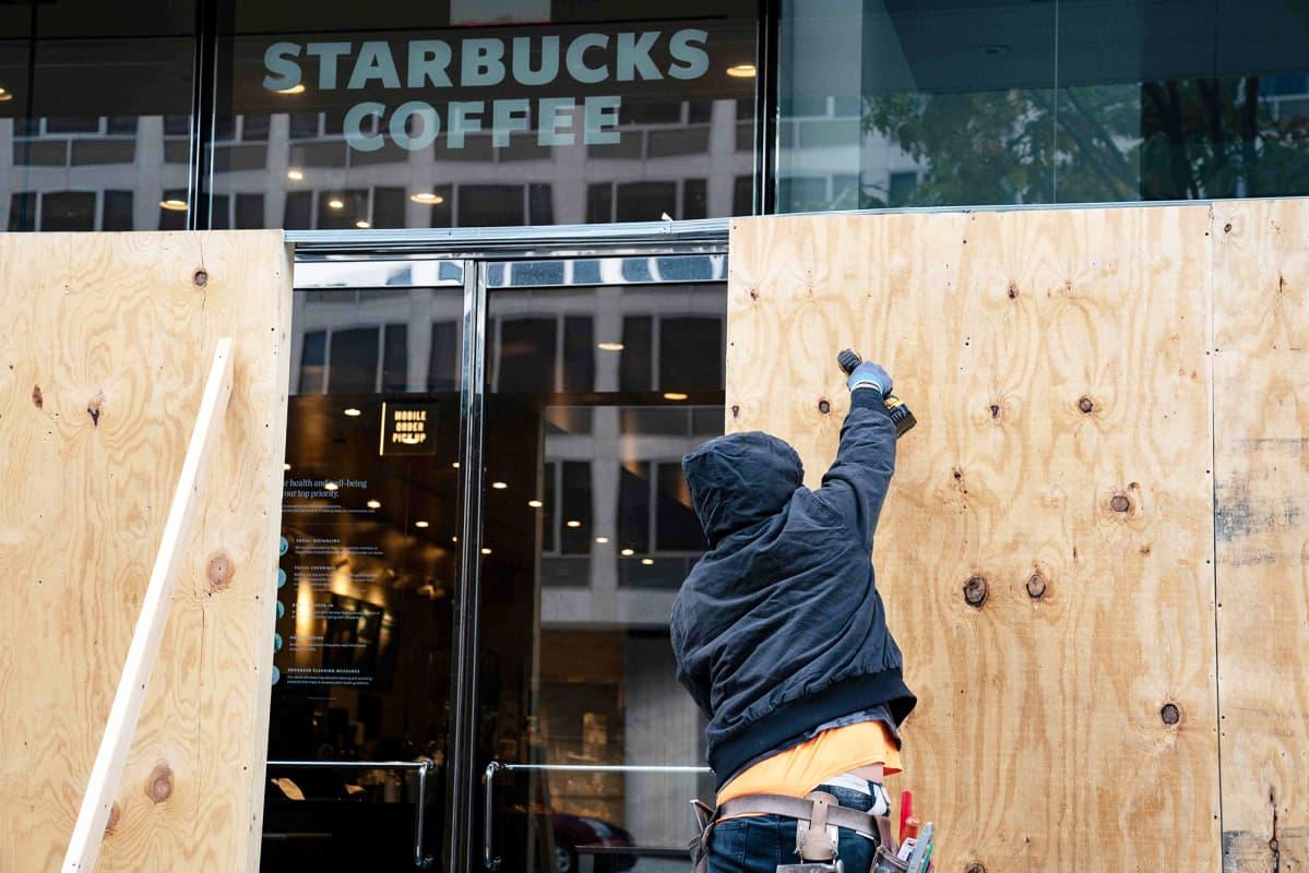 Työntekijä kiinnittää vanerilevyjä kahvilan ikkunoiden suojaksi.