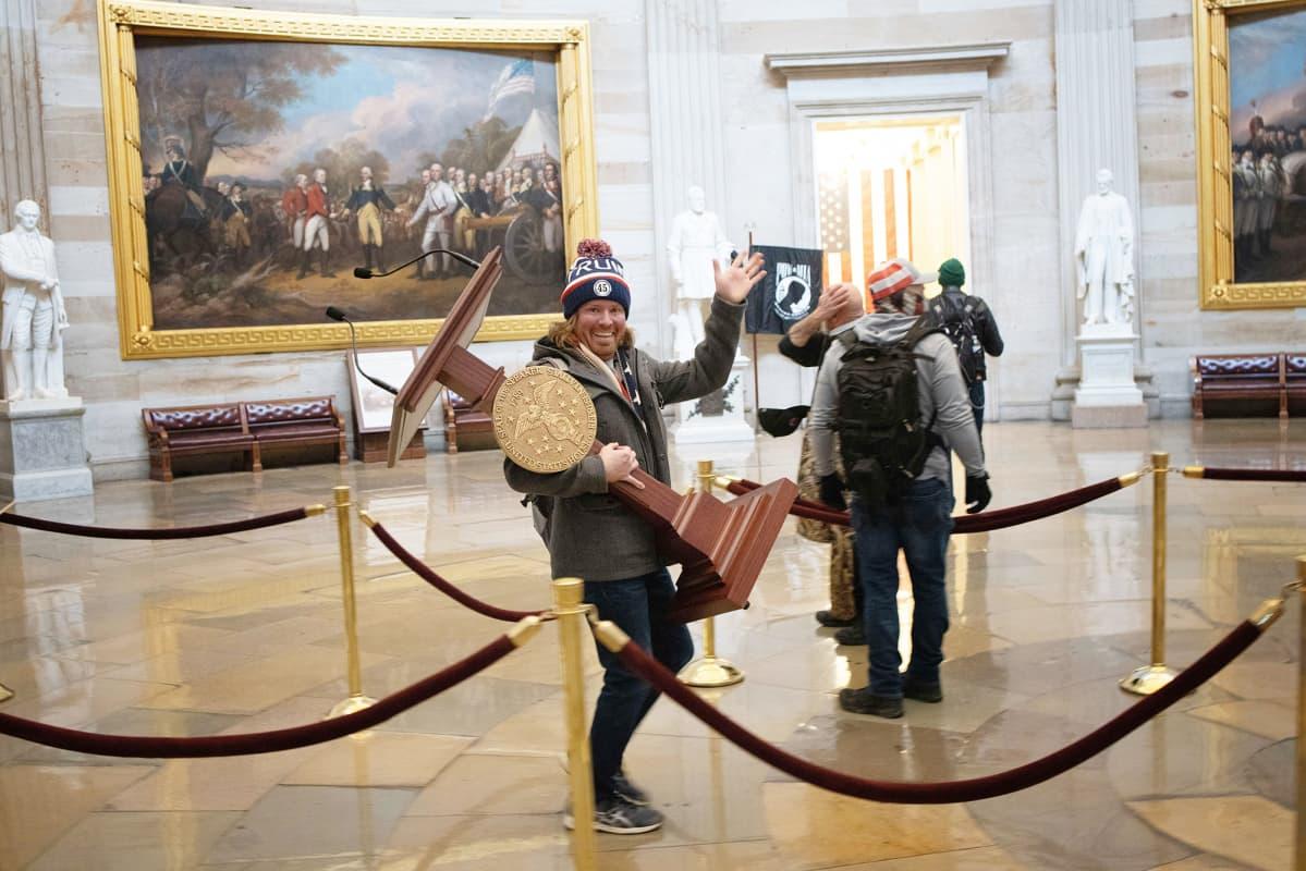Mies kantaa Nancy Pelosin kongressitalon puhujapönttöä.