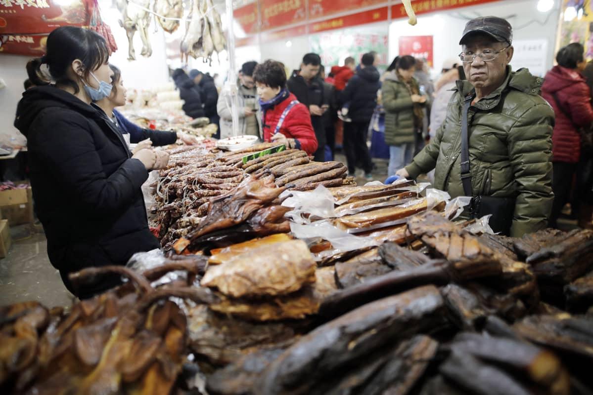 Asiakkaat ostavat lihatuotteija kiinalaisella ruokatorilla.