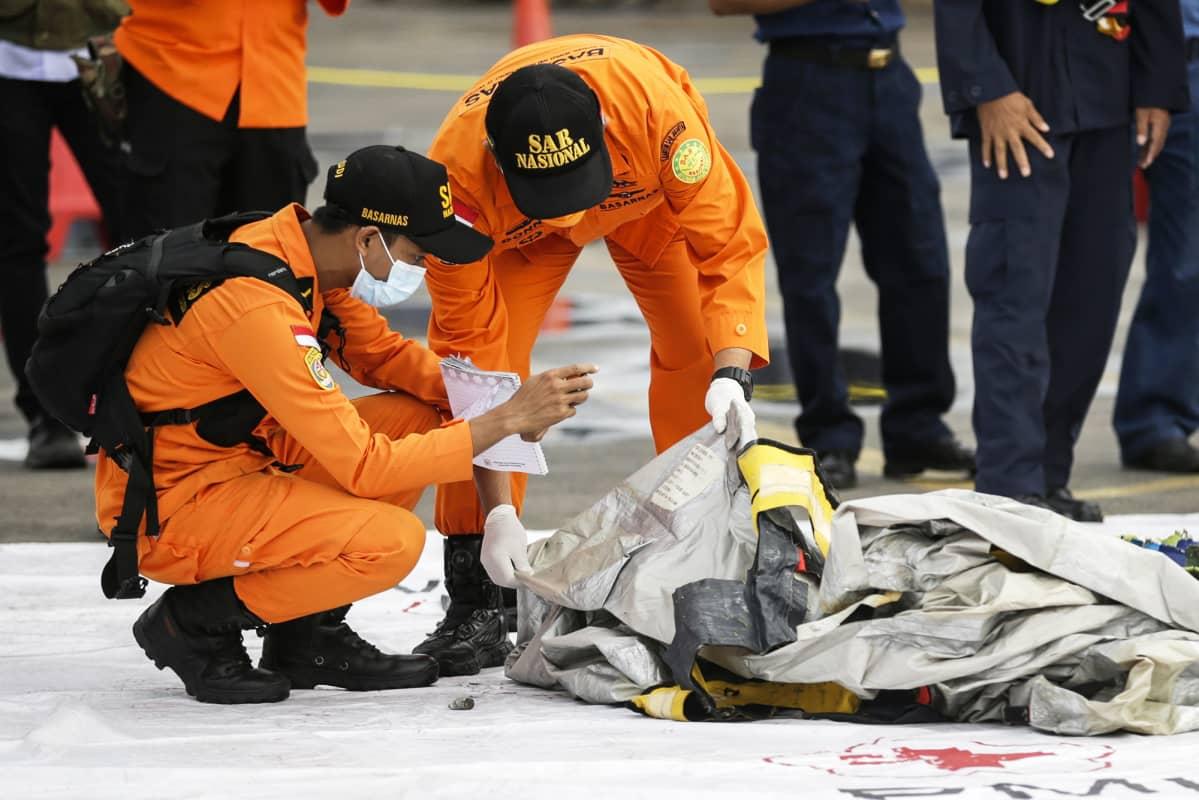 Pelastustyöntekijät tutkivat merestä löytyneitä lentokoneen osia.