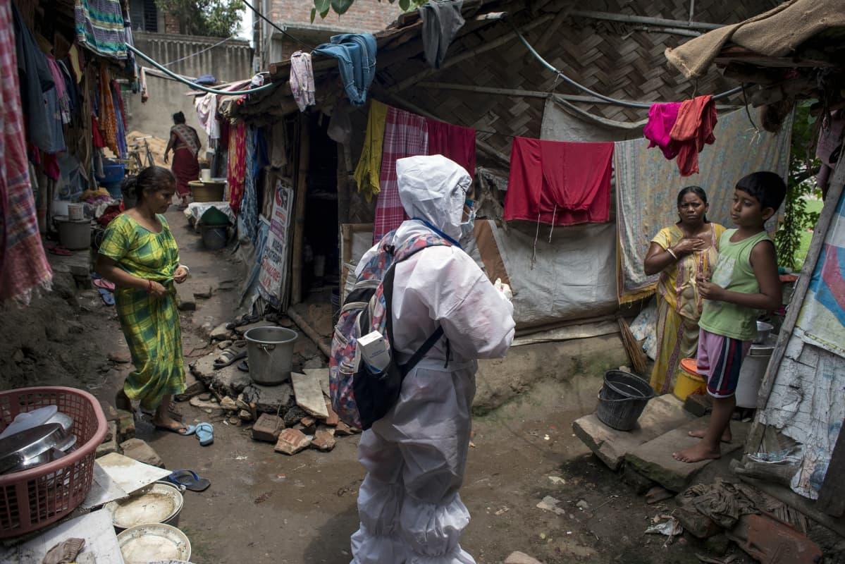 Suojapukuinen ihminen slummissa