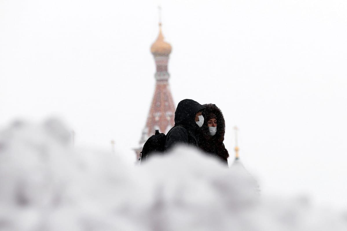 Kasvomaskeihin pukeutuneita ihmisiä Punaisella torilla Moskovassa.