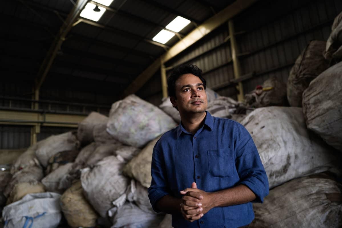 Mani Vajipey seisoo kädet ristissä teollisuushallissa. Hänen takanaan on kasassa suuria säkkejä.