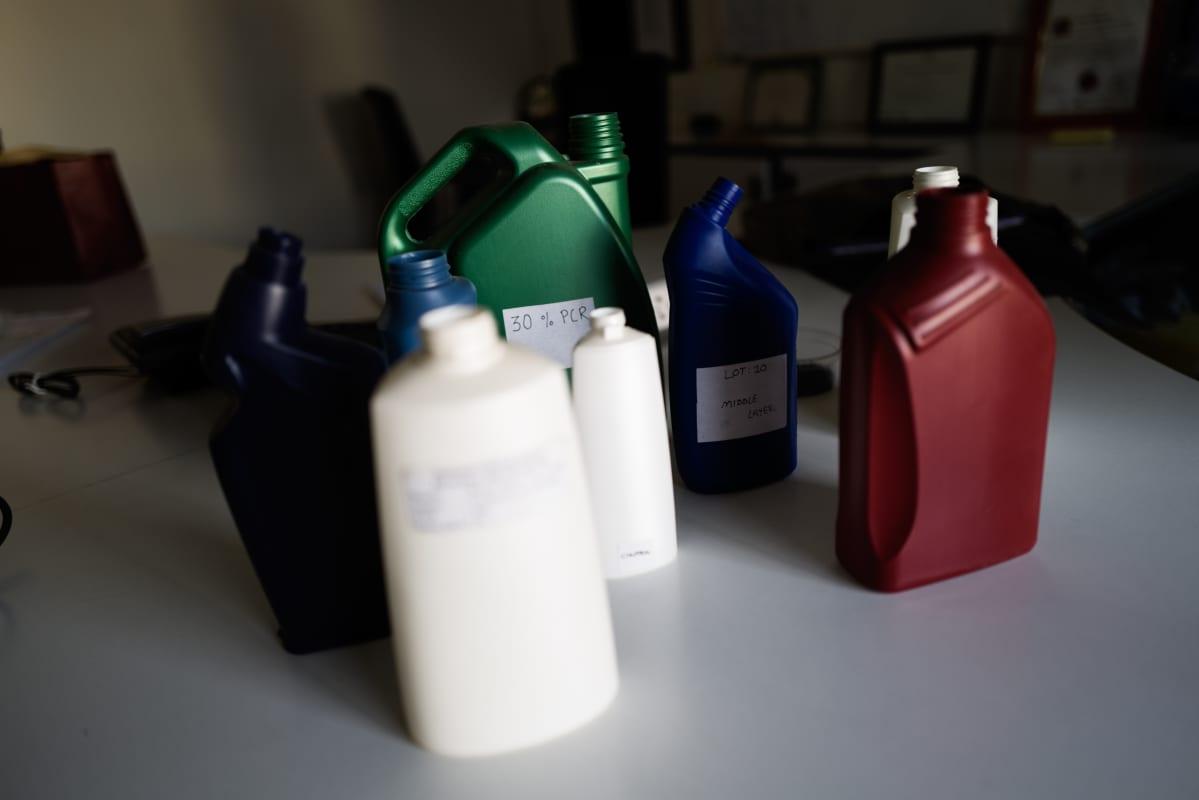 Erilaisia kierrätysmuovista valmistettuja tuotepakkauksia pöydällä.