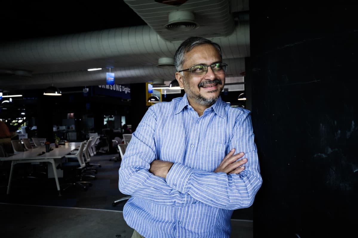 Ravi Narayan hymyilee ja nojaa T-Hubin toimiston seinään kädet puuskassa.