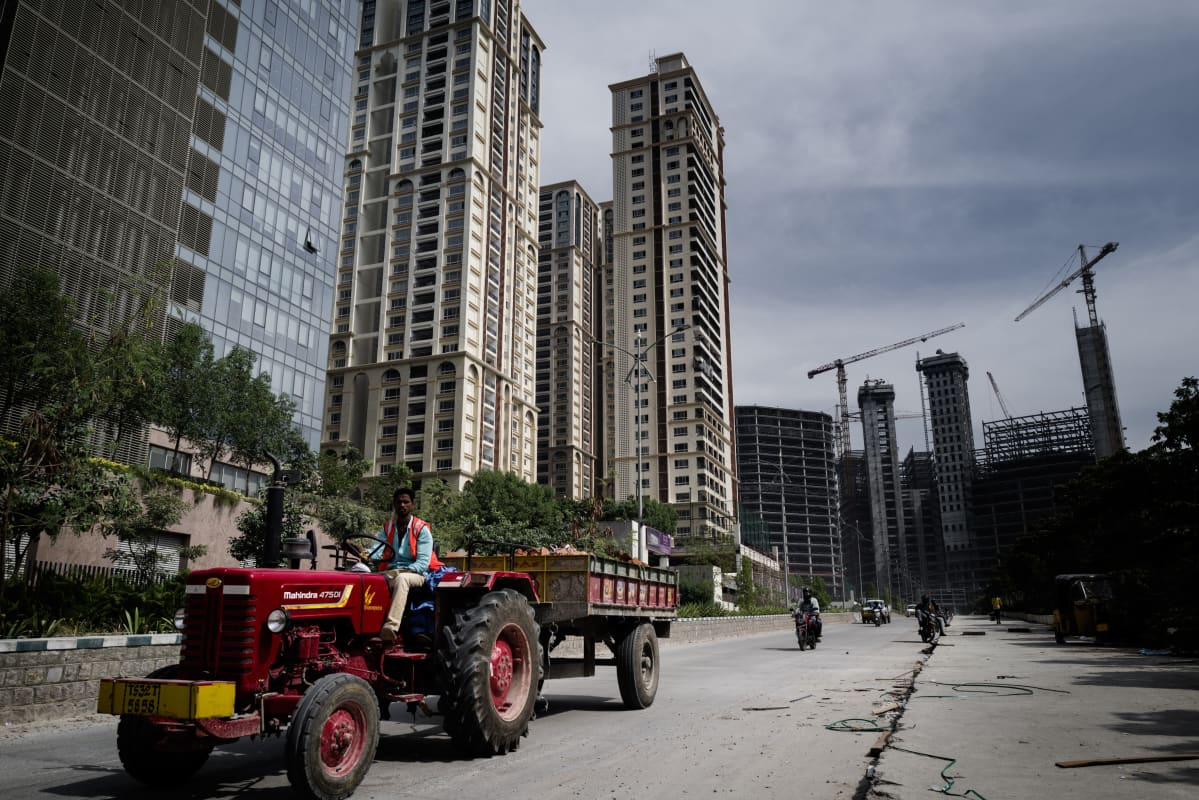 Mies ajaa peräkärryä vetävällä traktorilla. Vasemmalla puolella kohoaa tornitaloja ja taustalla näkyy uusia rakenteilla olevia torneja.
