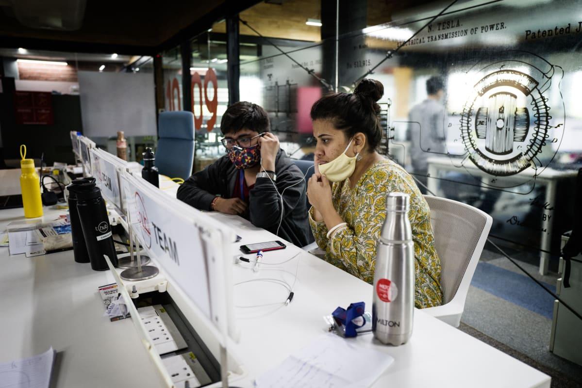 Mies ja nainen työskentelevät tietokoneella maskit kasvoillaan avokonttorissa.