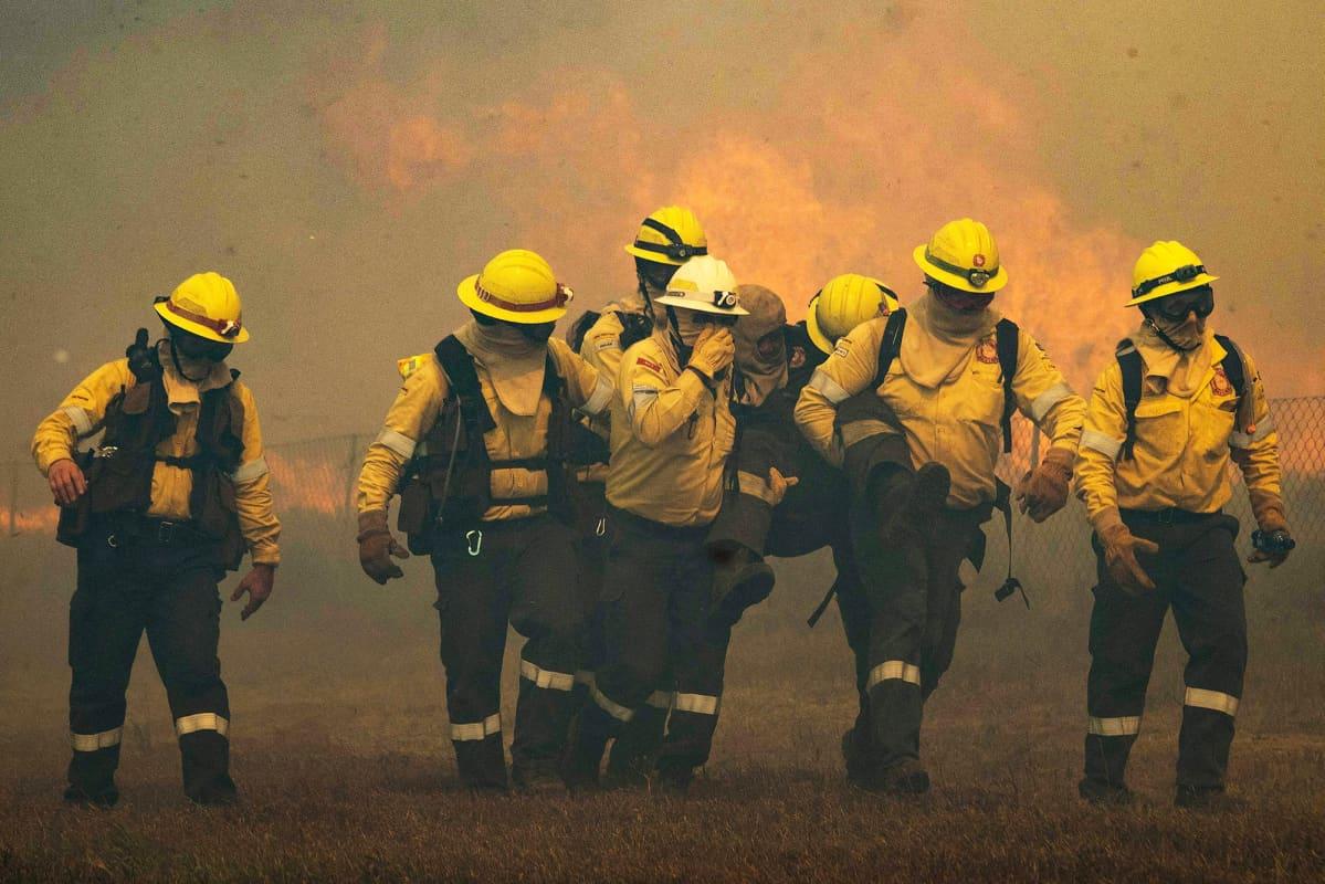 Palomiehet kantavat työkaveriansa.