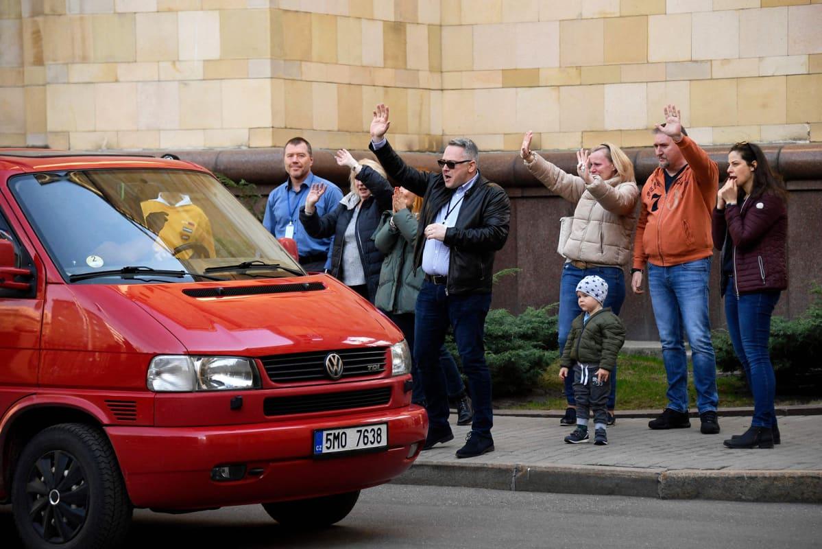 Tšekkiläiset diplomaatit vilkuttavat Moskovan suurlähetystön alueelta autolla poistuville.