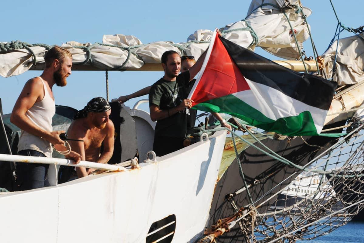 Miehistön jäsen heiluttaa Palestiinan lippua laivan kannella.