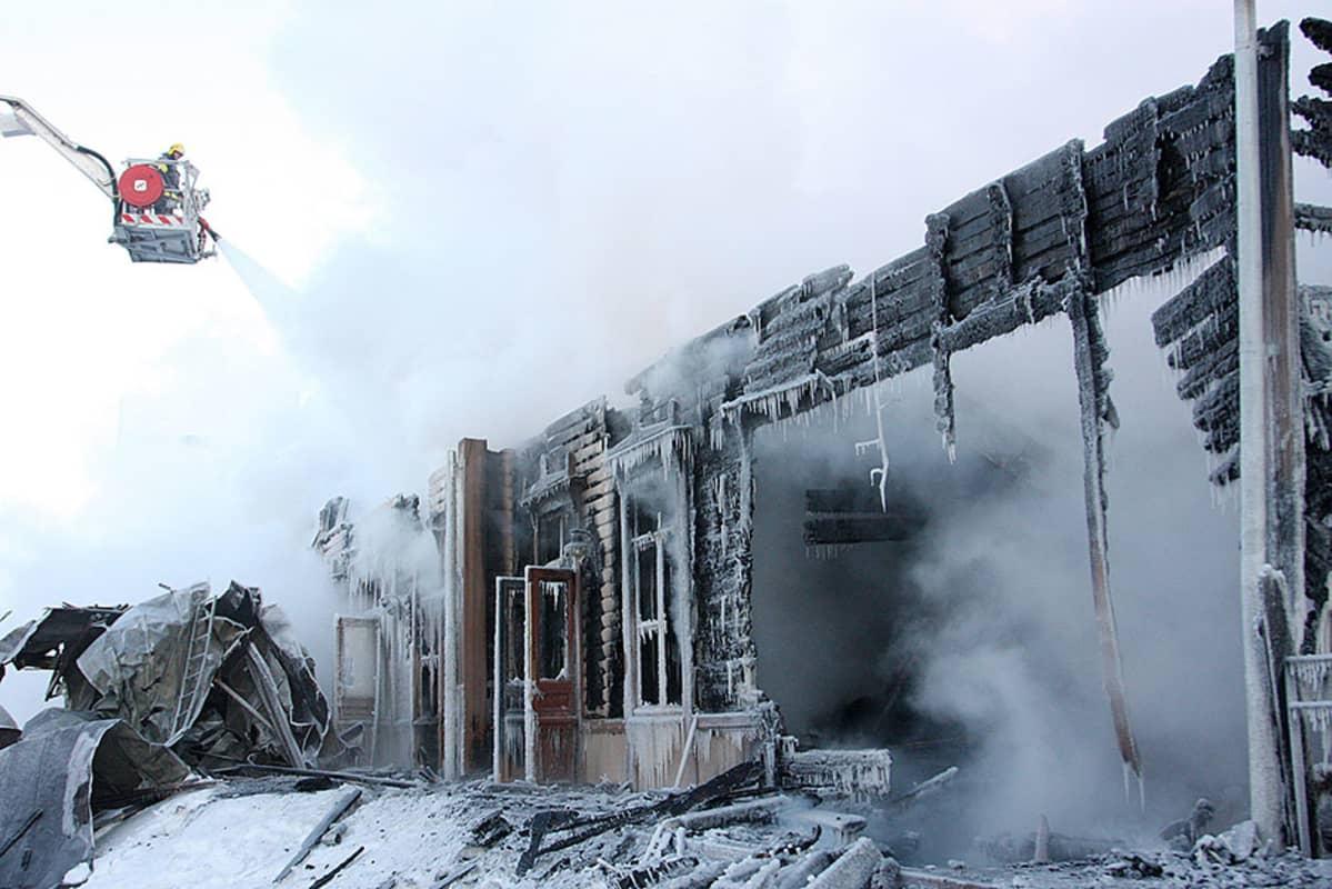 Palossa täysin tuhoutunutta rakennusta jälkisammutetaan. Kova pakkanen on jäädyttänyt sammutusveden