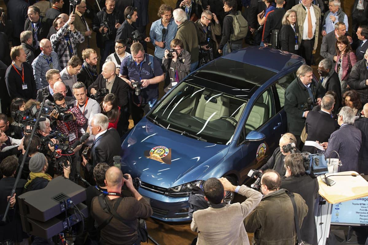 Volkswagen Golf ihmisten ympäröimänä autonäyttelyssä.