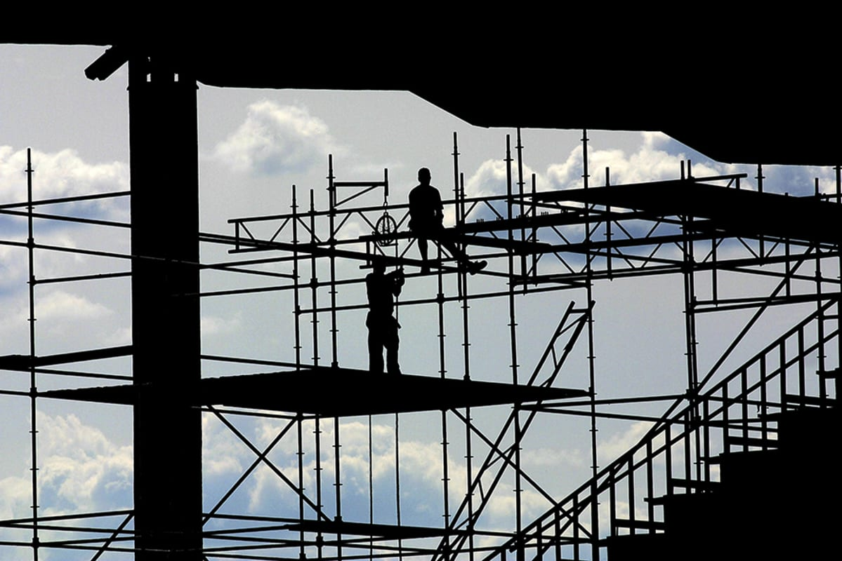 Miehiä rakennustelineillä.