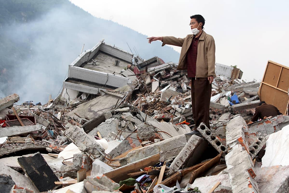 Kiinalainen mies osoittaa paikkaa pahoin maanjäristyksen runtelemalla alueella Kiinan Sichuanissa.