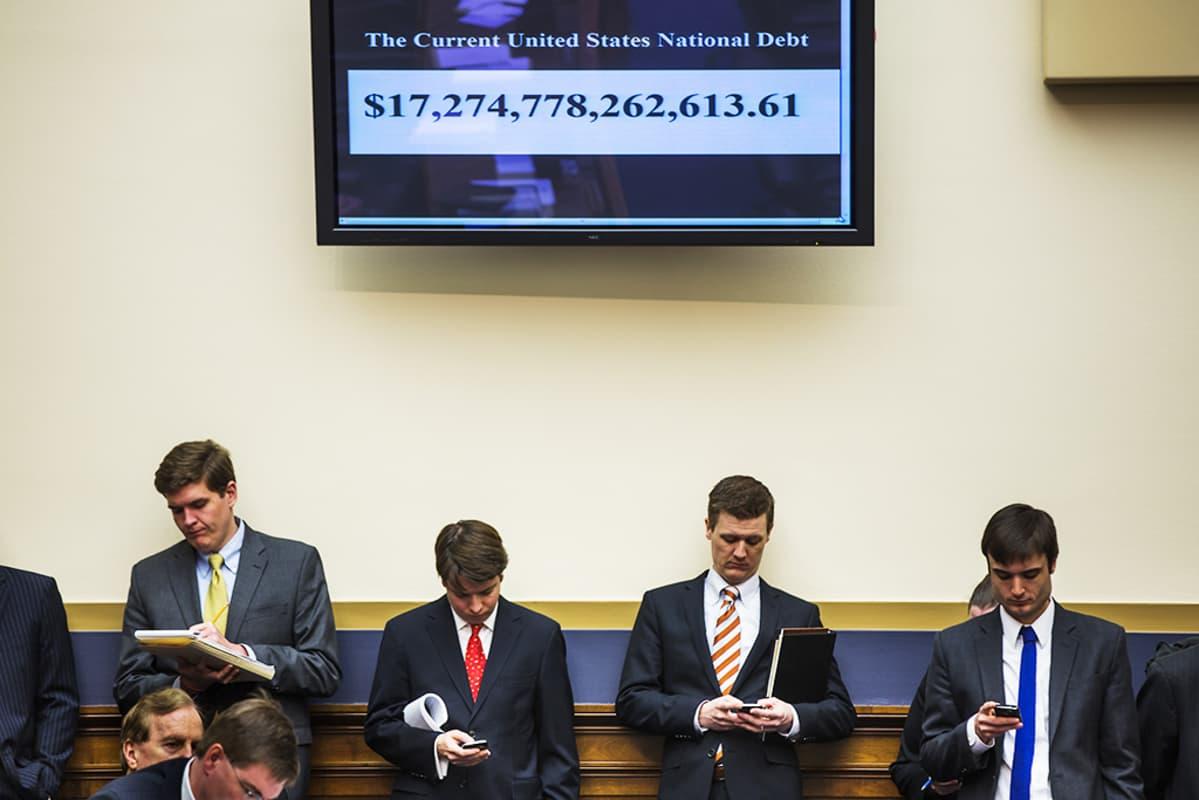 Edustajainhuoneen työntekijöitä Washingtonissa tiistaina, yläpuolellaan Yhdysvaltain velan määrän reaaliaikaisesti osoittava näyttö.