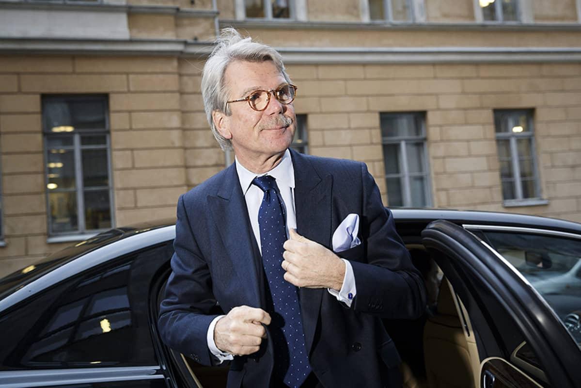 Björn Wahlroos astumassa ulos kadulle tummasta henkilöautosta.