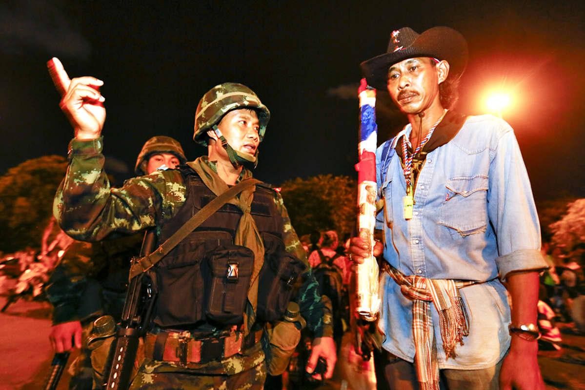 Sotilas keskustelee mielenosoittajan kanssa.
