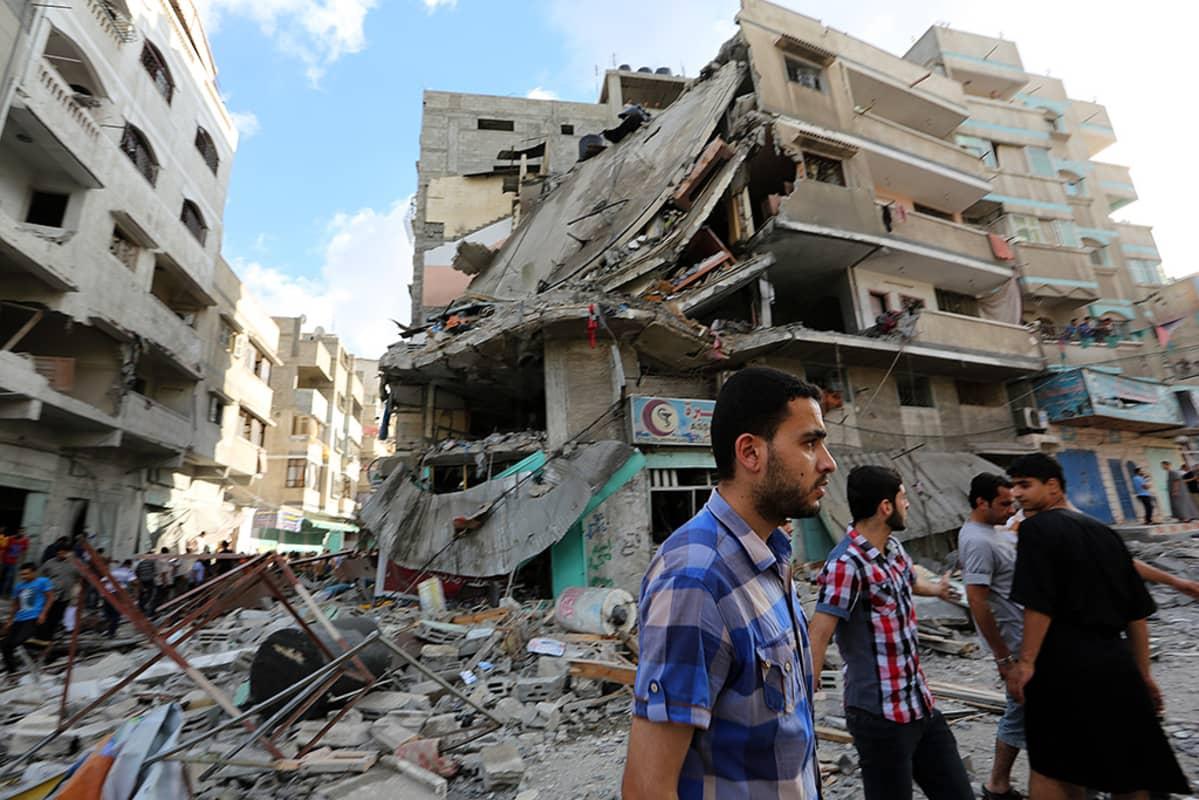 Palestiinalaismiehet tutkivat talojen raunioita Israelin ilmaiskun jälkeen Gazassa perjantaina 18. heinäkuuta 2014.