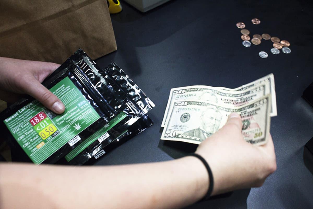 Top Shelf Cannabis -myymälän työntekijä ottaa vastaan asiakkaan rahoja Bellinghamissa, Washingtonin osavaltiossa, 8. heinäkuuta.