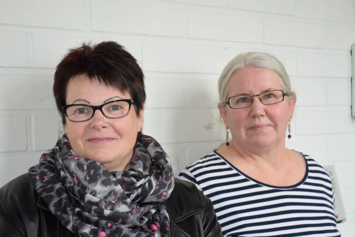 Kaksi naista kuvassa seinää vasten