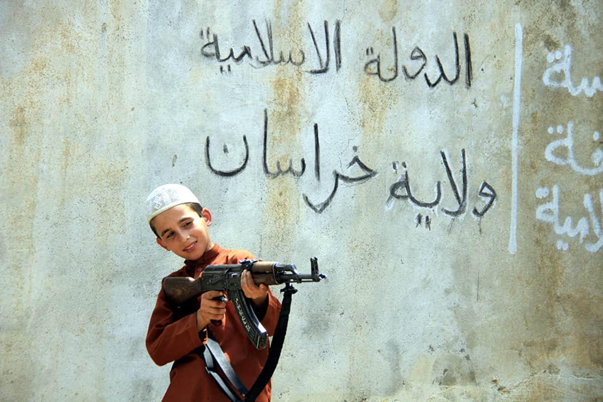 Lapsisotilas tähtäilee rynnäkkökiväärillä.