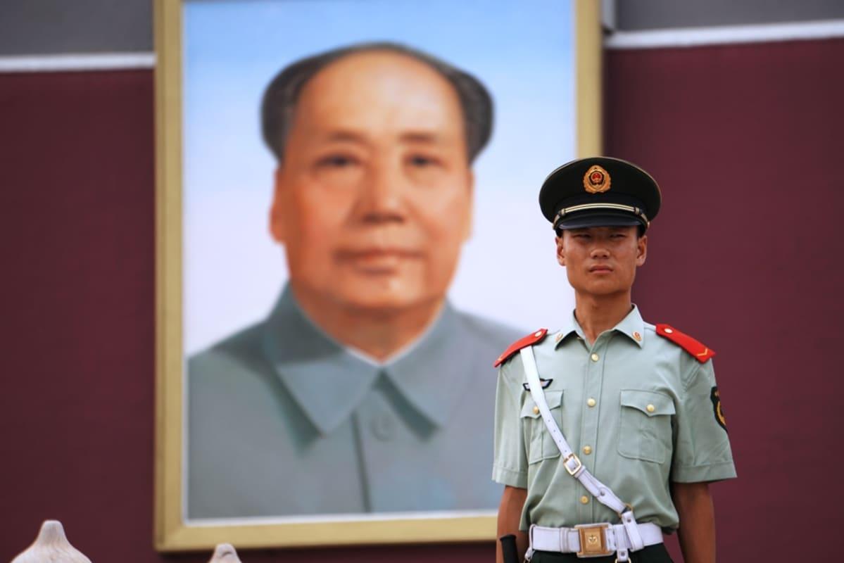 Kiinalainen sotilas Maon kuvan edessä.
