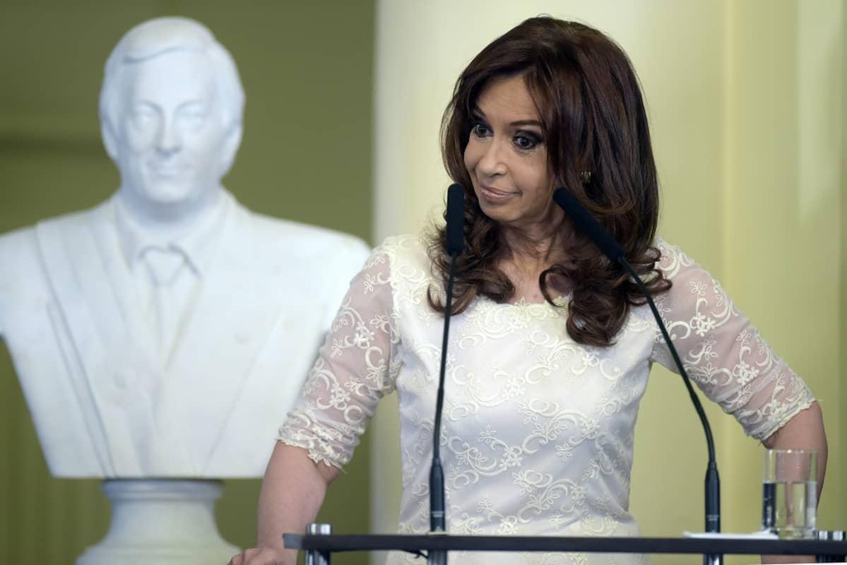 Cristina Fernandez de Kirchner. Taustalla hänen edesmennyttä miestään Nestor Kirchneriä esittävä rintakuva.