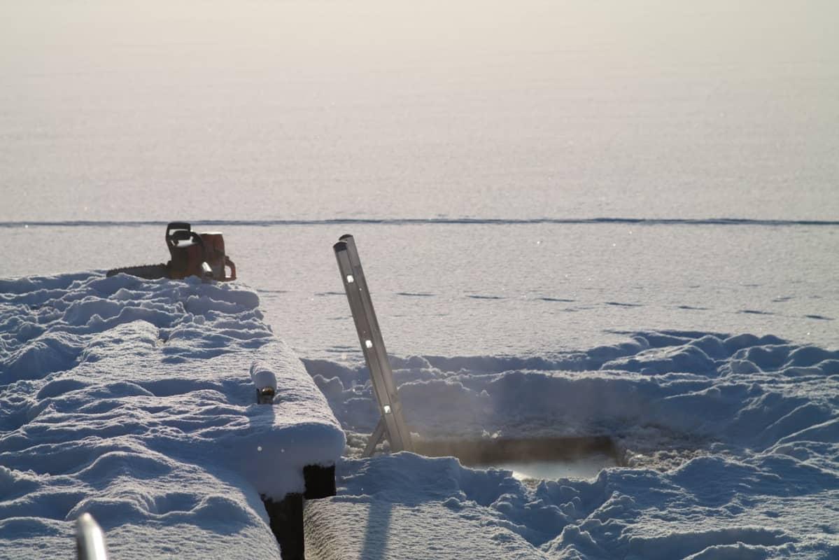 Avanto höyryää, alumiinitikkaat johtavat järveen.