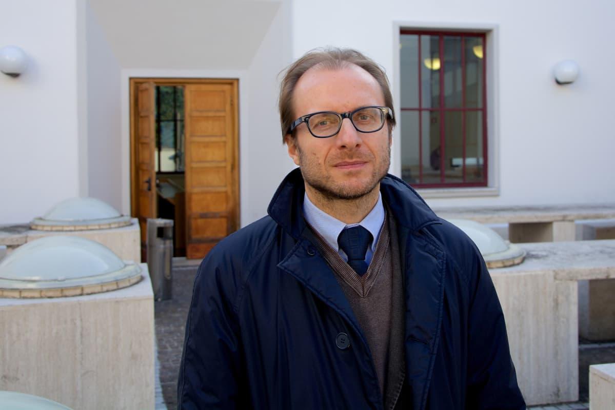 Silmälasipäinen dosentti Gino Scaccia sinisessä trenssitakissaan valkoisen rakennuksen luona.