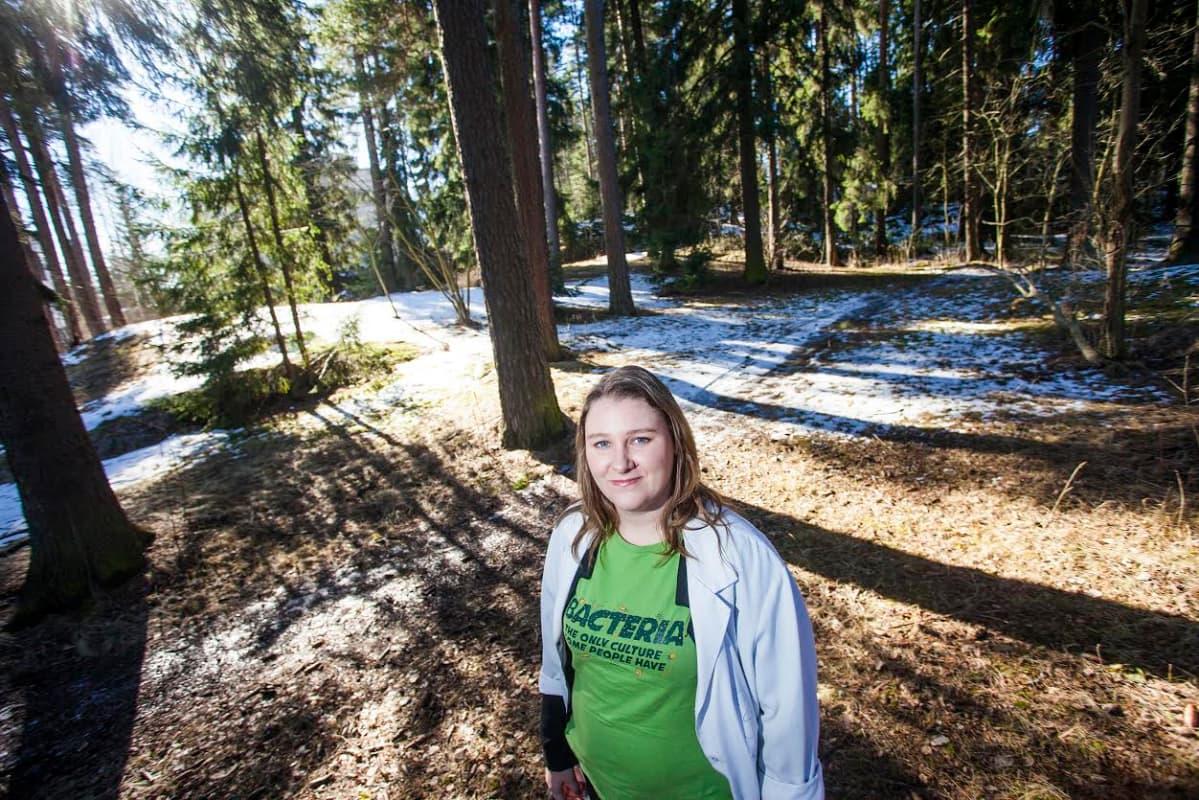 Alzheimertutkija Eloise Mikkonen seisoo puiden keskellä metsässä.