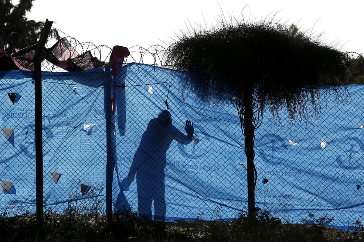 Mies katsoo aidan takaaa pakolaileirillä.