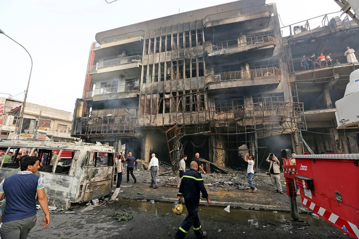 Pelastustyöntekijät raivaavat autopommi-iskun jälkiä.