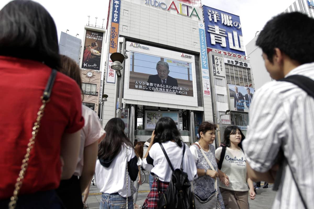 Tokiolaiset seuraavat keisarin puhetta kadulla