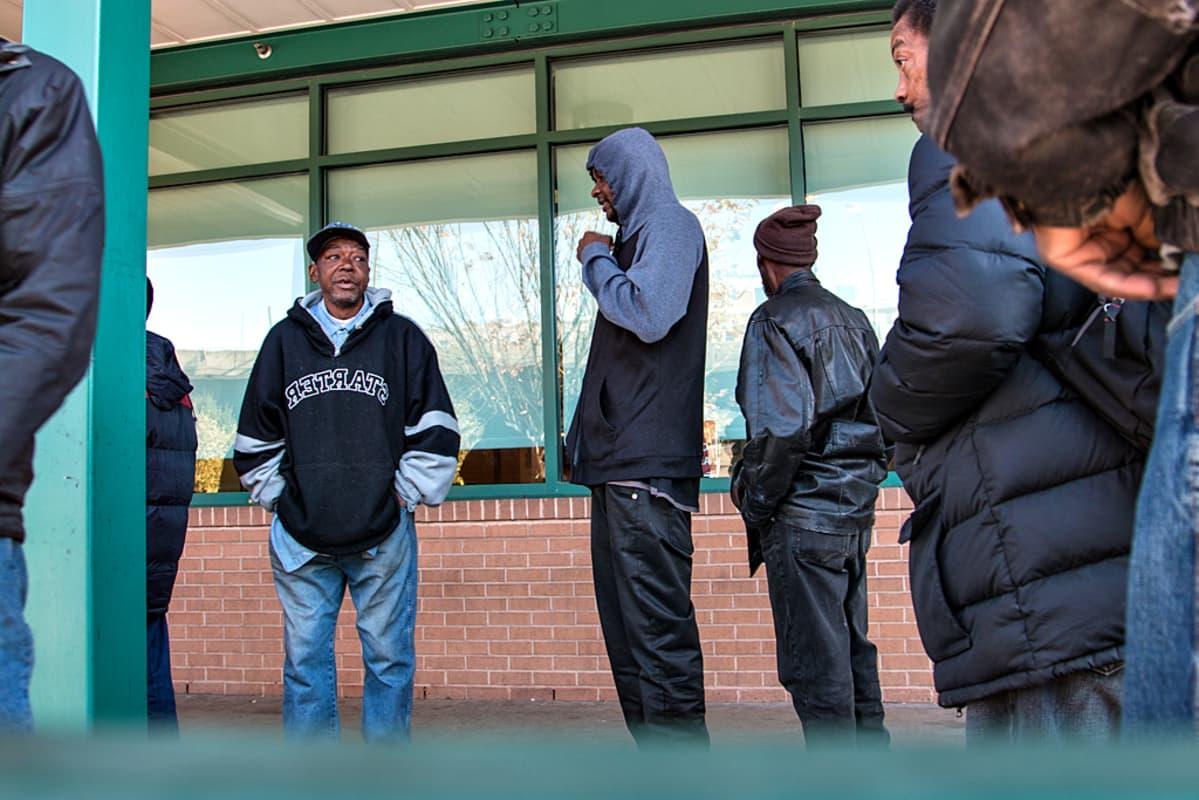Mustaihoisia miehiä seisoskelee jonossa.
