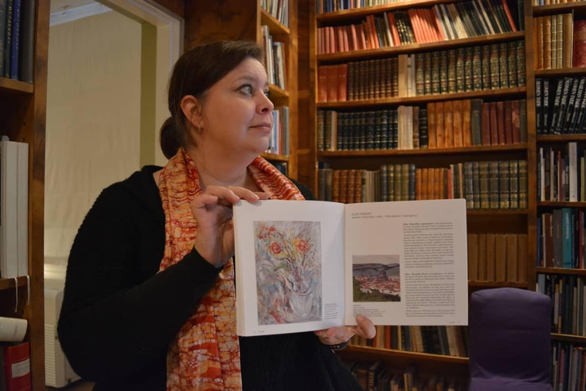 Ellen Thesslefin maalaama kukka-asetelma löytyy myös monista taidekirjoista. Vaasan vt Museotoimenjohtaja Selma Green näyttää tässä yhtä.