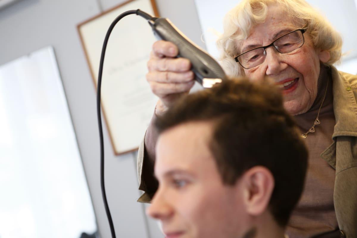 Nainen leikkaa miehen hiuksia koneen avulla.