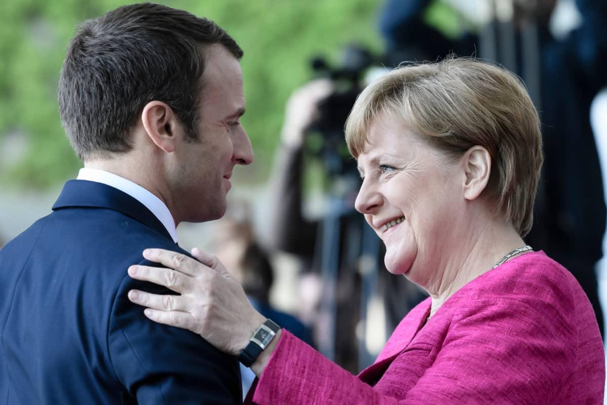 Macron ja Merkel tervehtivät.